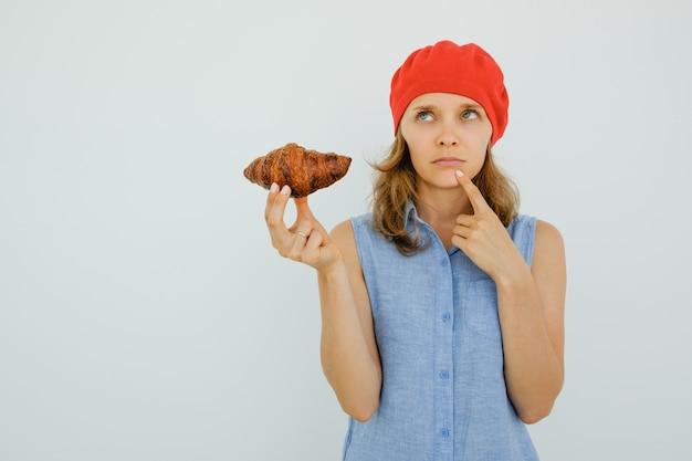 Peinzende nice woman holding heerlijke croissant