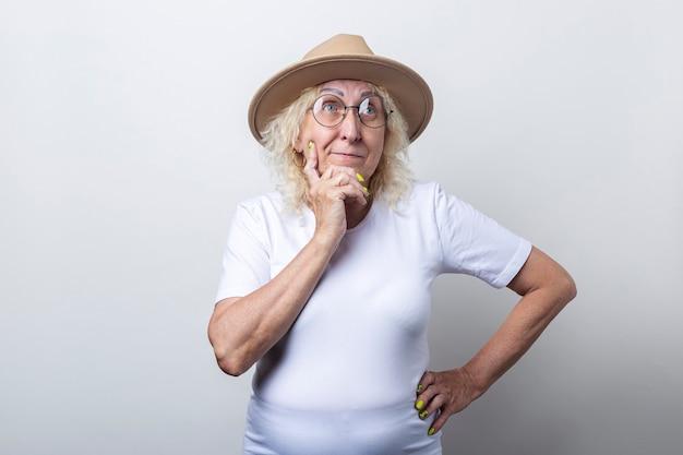 Peinzende oude vrouw in een hoed die haar hand op haar kin houdt op een lichte achtergrond.