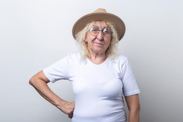 Peinzende oude vrouw in een hoed met een bril op een lichte achtergrond.