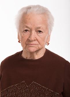 Peinzende oude vrouw op een wit