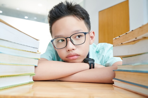 Peinzende preteen jongen die in glazen grote stapels boeken op zijn bureau bekijkt