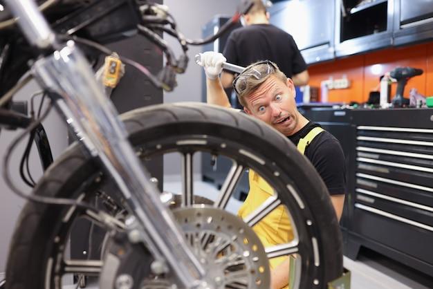 Peinzende slotenmaker houdt een moersleutel vast en kijkt naar het reparatieconcept van het motorwiel