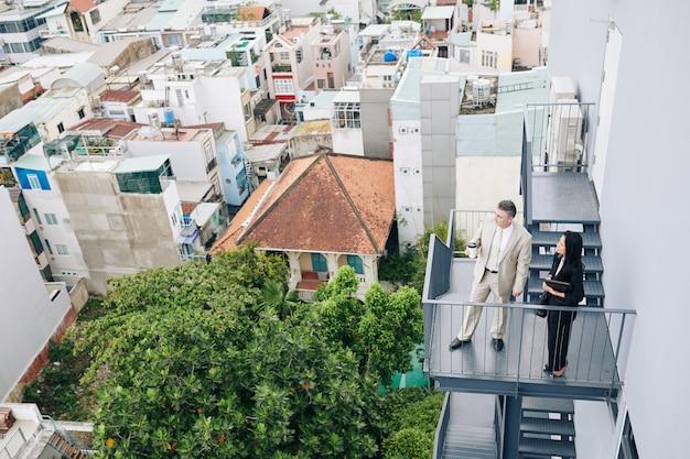 Peinzende succesvolle ondernemers die op de brandtrap staan en naar de stad kijken tijdens de koffiepauze