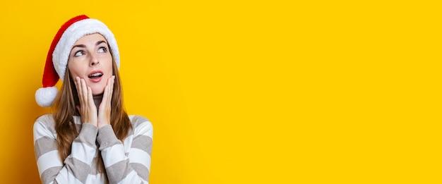 Peinzende verraste jonge vrouw in de hoed van de kerstman op een gele achtergrond. banier.