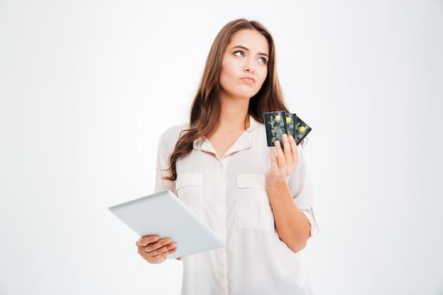 Peinzende vrouw die creditcard houdt en tabletcomputer gebruikt die op een witte muur wordt geïsoleerd