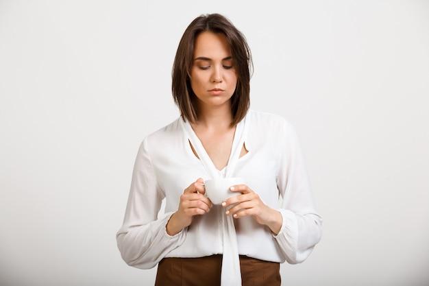 Peinzende vrouw die droevige kop van koffie bekijkt