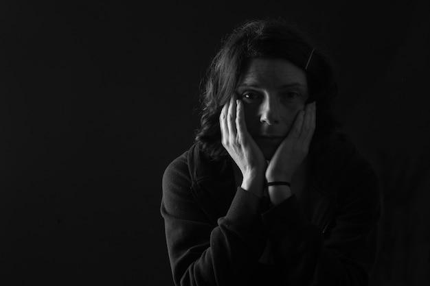 Peinzende vrouw die met beide handen op haar gezicht camera op zwarte achtergrond bekijkt