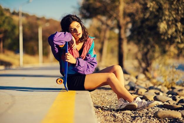 Peinzende vrouw die op de baan zit en een skateboard vasthoudt