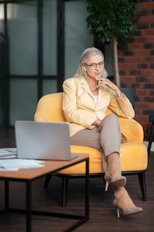Peinzende vrouw. doordachte stijlvolle zakenvrouw zittend in een comfortabele gele fauteuil in haar kantoor terwijl ze naar een laptop kijkt