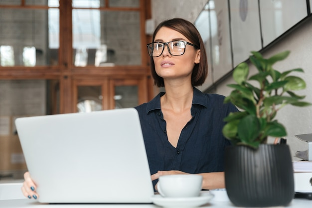 Peinzende vrouw in oogglazen die met laptop computer werken