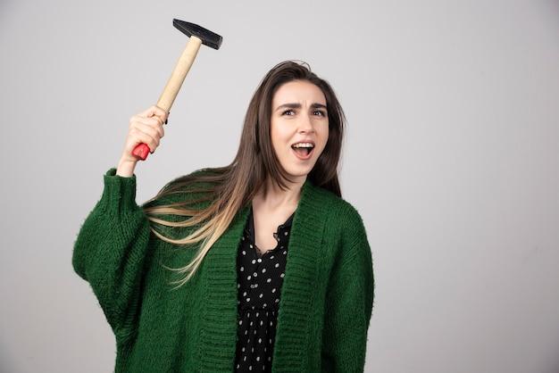 Peinzende vrouw met hamer in handen op een grijze achtergrond.