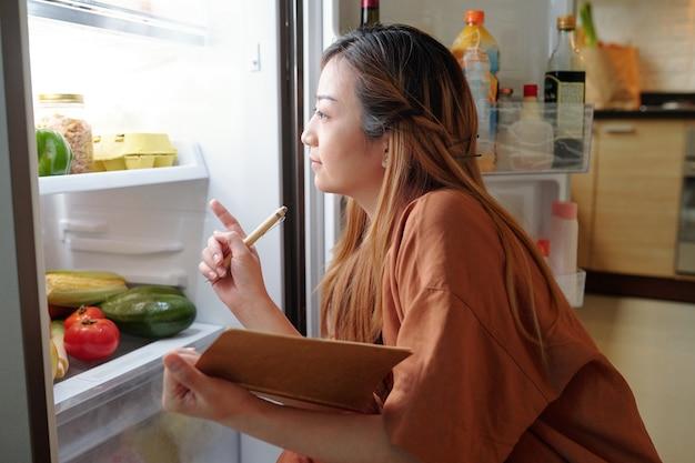 Peinzende vrouw met notitieblok die boodschappen in haar koelkast controleert en een lijst opschrijft met producten die ze moet kopen