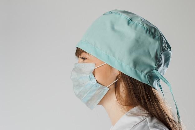 Peinzende vrouwelijke arts of verpleegster die beschermend masker en glb draagt