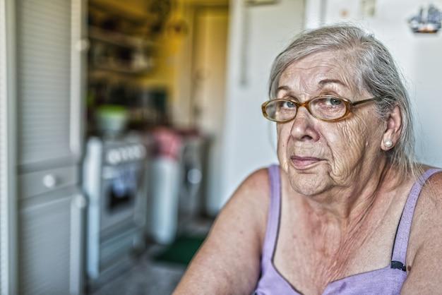 Peinzende vrouwelijke pensioenaris die naar de camera kijkt