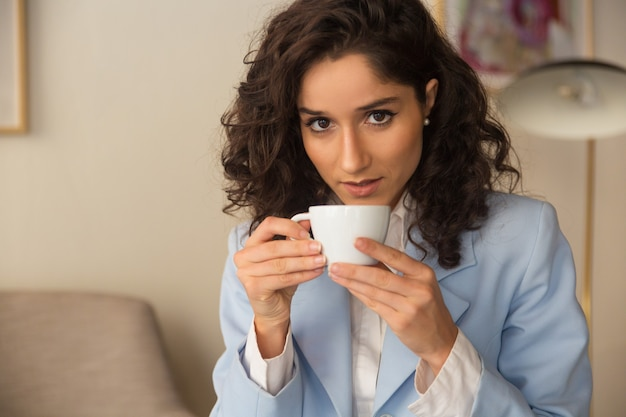 Peinzende vrouwelijke professionele koffie thuis drinken
