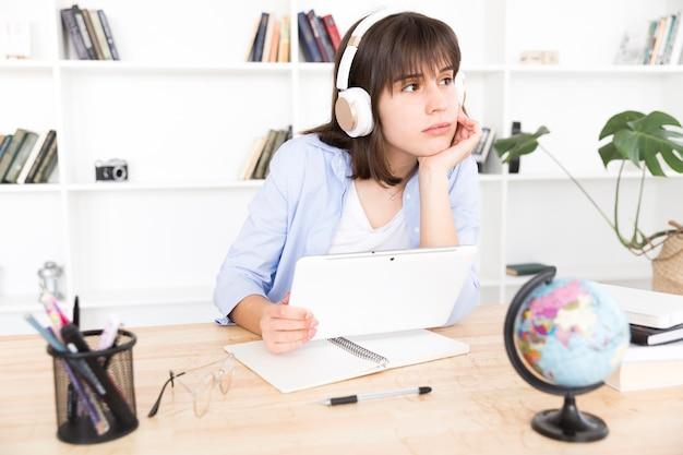 Peinzende vrouwelijke student die aan muziek luistert