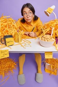 Peinzende vrouwelijke student schrijft notities op stickers maakt schema voor weekdagen doet huiswerktaak thuiskantoor zit op rommelige desktop bereidt cursussenplan voor creats artikel voor persoonlijke blog