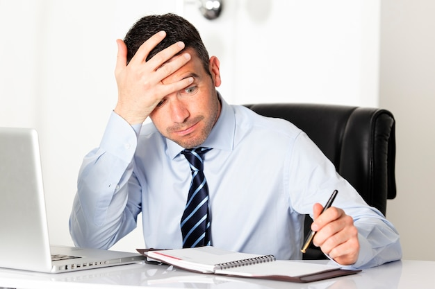 Peinzende zakenman die zijn notitieboekje kijkt