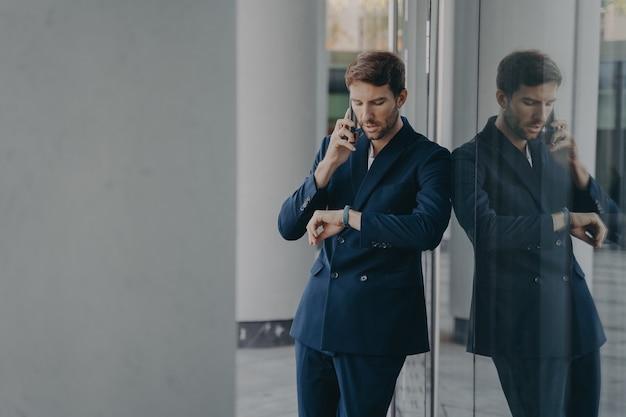 Peinzende zakenman in pak die op mobiele telefoon praat die buiten staat en naar zijn handhorloge kijkt