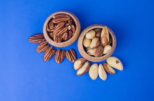Pekan en paranoten op blauwe achtergrond. gezond eten