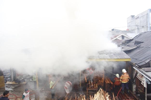 Pekanbaru indonesië 1 augustus 2015 brandweerlieden proberen een brand te blussen die een gemeenschap overspoelt