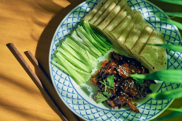 Peking varkensvlees of eend met komkommersalade en chinees brood op een bord. chinese keuken
