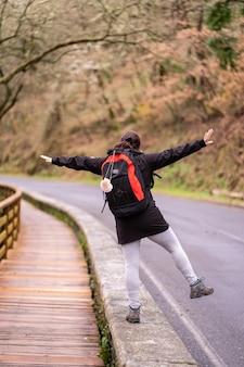 Pelgrim brunette vrouw springen en spelen op de top van een muur die de camino de santiago doet