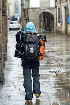 Pelgrim die op regenachtige dagstraat loopt van oude stad van santiago de compostela