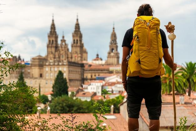 Pelgrim kijkt naar de kathedraal van santiago de compostela in spaink, rugzak op zijn rug