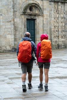 Pelgrims die op regenachtige dag in oude stad van santiago de compostela lopen