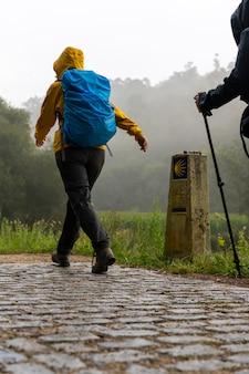 Pelgrims lopen op weg naar st. james (santiago) op een mistige dag in galicië