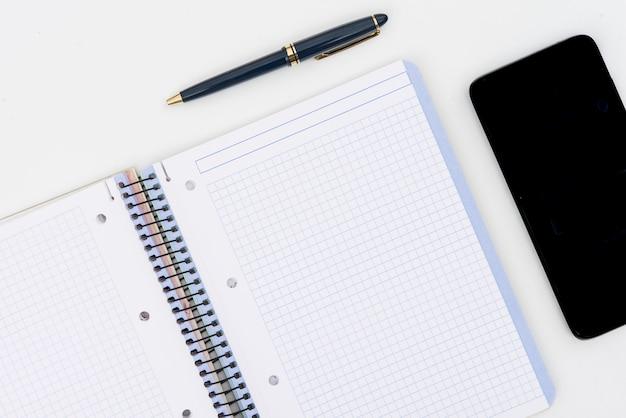 Pen, blocnote en mobil met houten raadselstukken op witte achtergrond