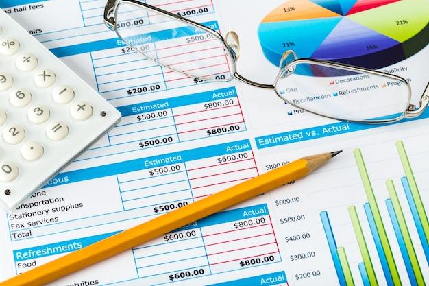 Pen, bril en rekenmachine op zakelijke grafieken en diagrammen