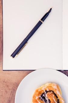 Pen en blocnote door zoet voedsel in plaat op lijst