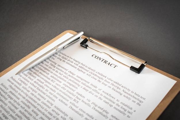 Pen en contractdocumenten op houten bureau