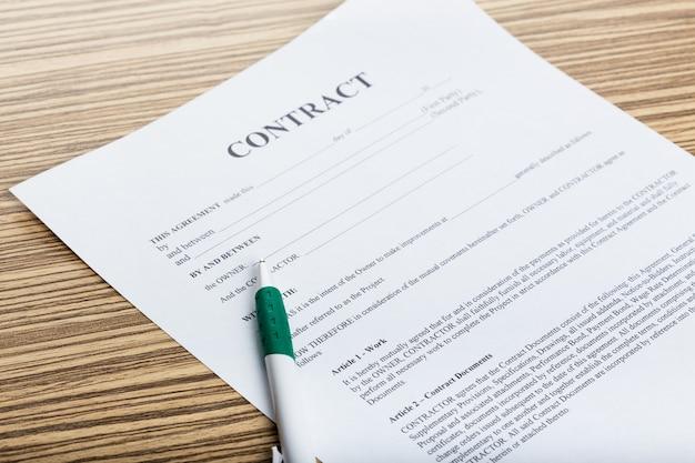 Pen en contractpapieren op houten bureau