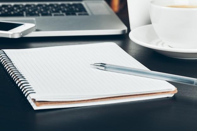 Pen en notitieblok van dichtbij op een bureau