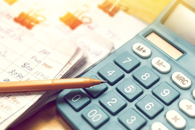 Pen en papier van thuisbudget maandelijks met calculator