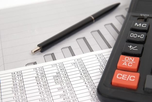 Pen en rekenmachine op papieren tafel met financiële diagram