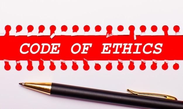 Pen en witte gescheurde papieren strook op een felrode achtergrond met de tekst code of ethics
