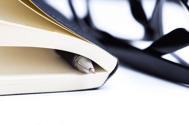 Pen, glazen en notebook close-up