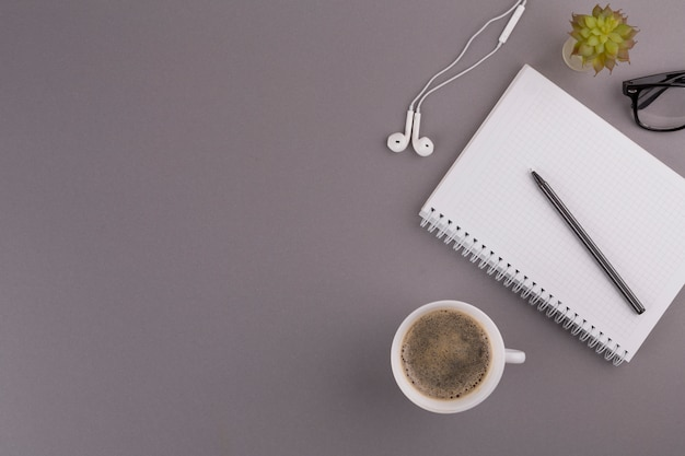 Pen in de buurt van kladblok, beker, oortelefoons en bril
