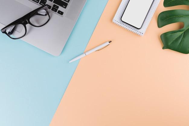 Pen in de buurt van kladblok, smartphone, plant, bril en laptop