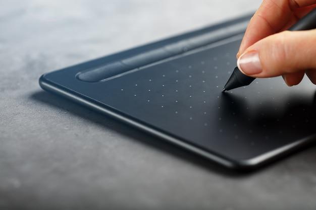 Pen met een grafisch tablet in de handen van de ontwerper, close-up. gadget voor kunst en werk.