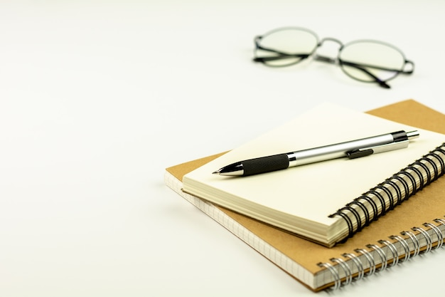 Pen op dagboekboek en glazen op witte bureauachtergrond.
