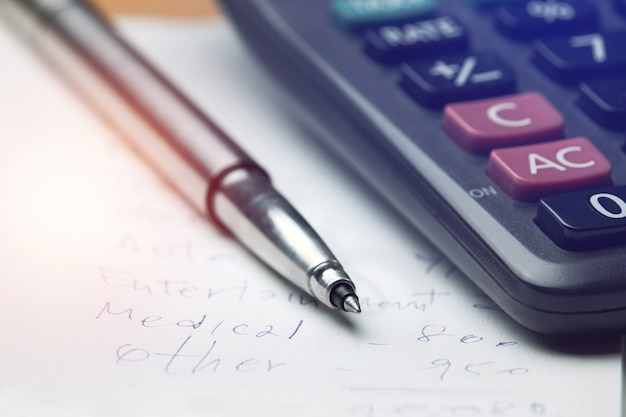 Pen op huishoudelijk rekeningpapier, persoonlijke uitgaven maandelijks, thuisbudget met rekenmachine