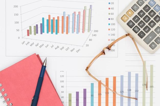 Pen op notitieboekje met glazen en calculator op grafiek wordt geplaatst die
