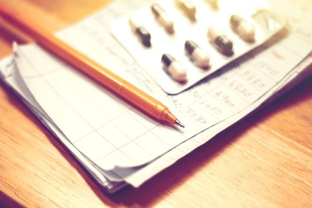 Pen op papier blad van medicijnkosten. budget voor aangeboren ziekte
