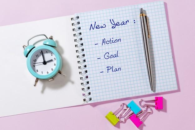 Pen, papier met nieuwjaar, actie, doel, plan en blauwe wekker op lichtroze