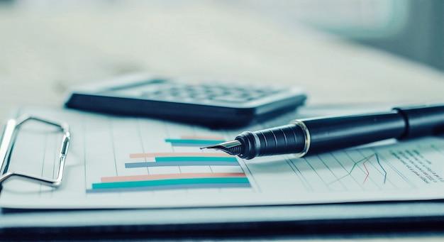 Pen, rekenmachine en financiële grafiek op een werkplek van het bedrijf